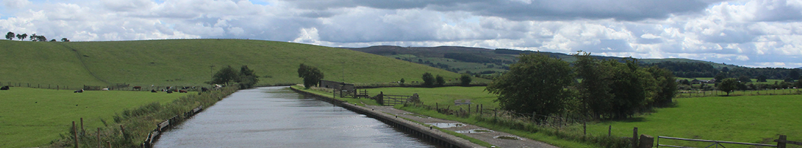 Canal in England surrounded by green hills of Yorkshire The scenic route of the Leeds to Liverpool canal going towards Gargrave, to the backdrop of the Yorkshire Dales.